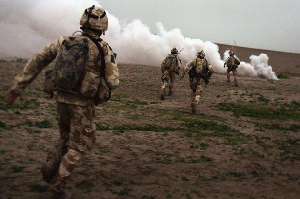 British Marines run towards a Taliban position during a British commando offensive